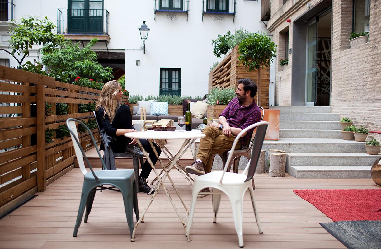 Sillas icónicas, tarima de madera y mesas de forja visten la terraza del Toc Hostel Sevilla