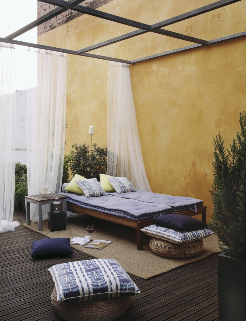 Mediterranean patio area with bed, floor pillows and elegant mosquito net