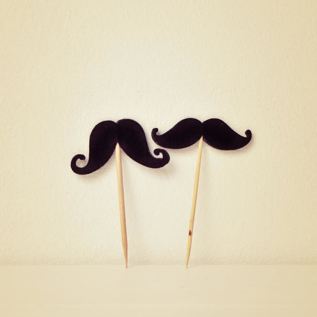 two different felt mustaches in sticks over a beige background, with a retro effect