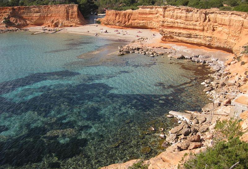 Ibiza stupisce per i colori dei suoi paesaggi, una palette cromatica in equilibrio tra il blu intenso del mare, il rosso della terra e il verde della macchia mediterranea. Un gioco di nuance evidente nel panorama di Sa Caleta.