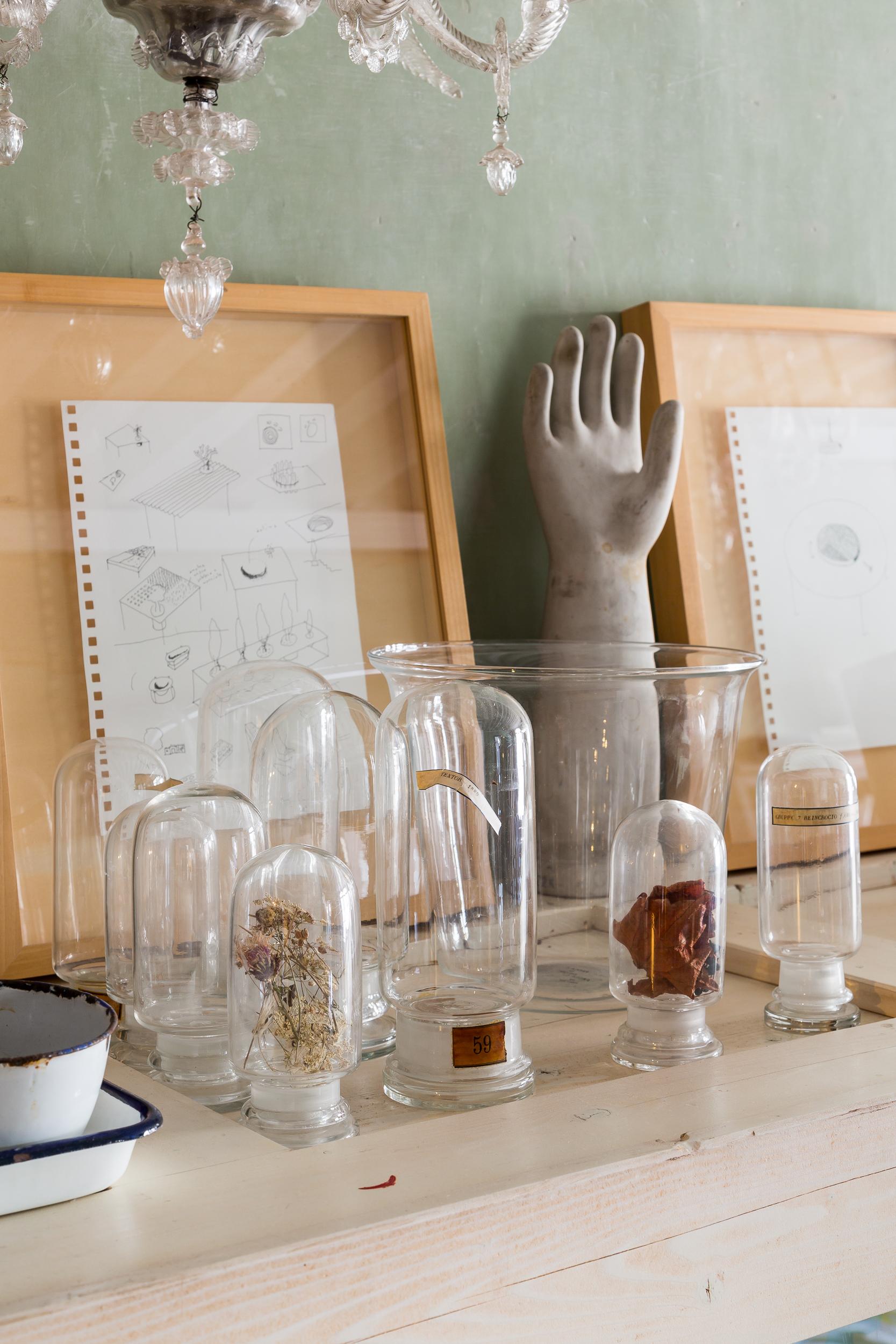 Un antico stampo utilizzato per la realizzazione di guanti diventa un elemento dal grande fascino retrò, esaltato dall'abbinamento con le classiche ampolle da farmacia in vetro.