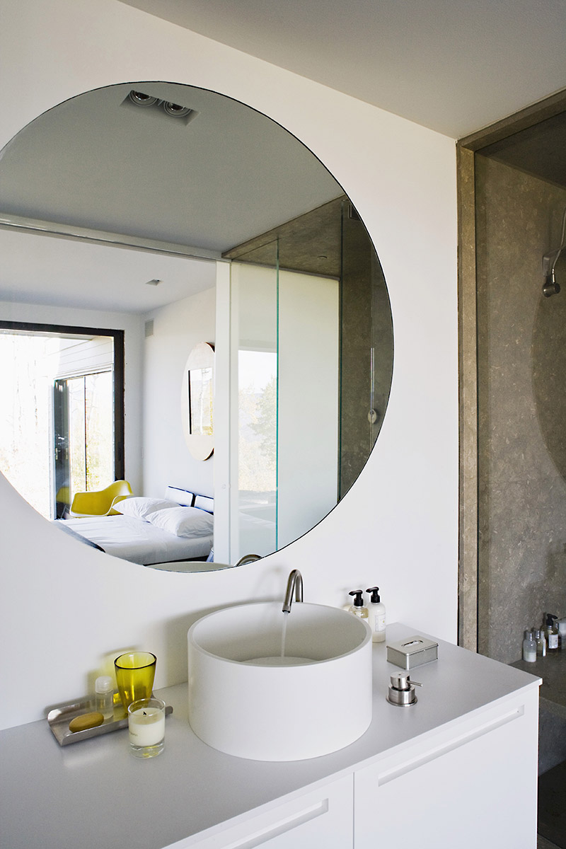 A white designer wash stand with bathing utensils and a round wall mirror
