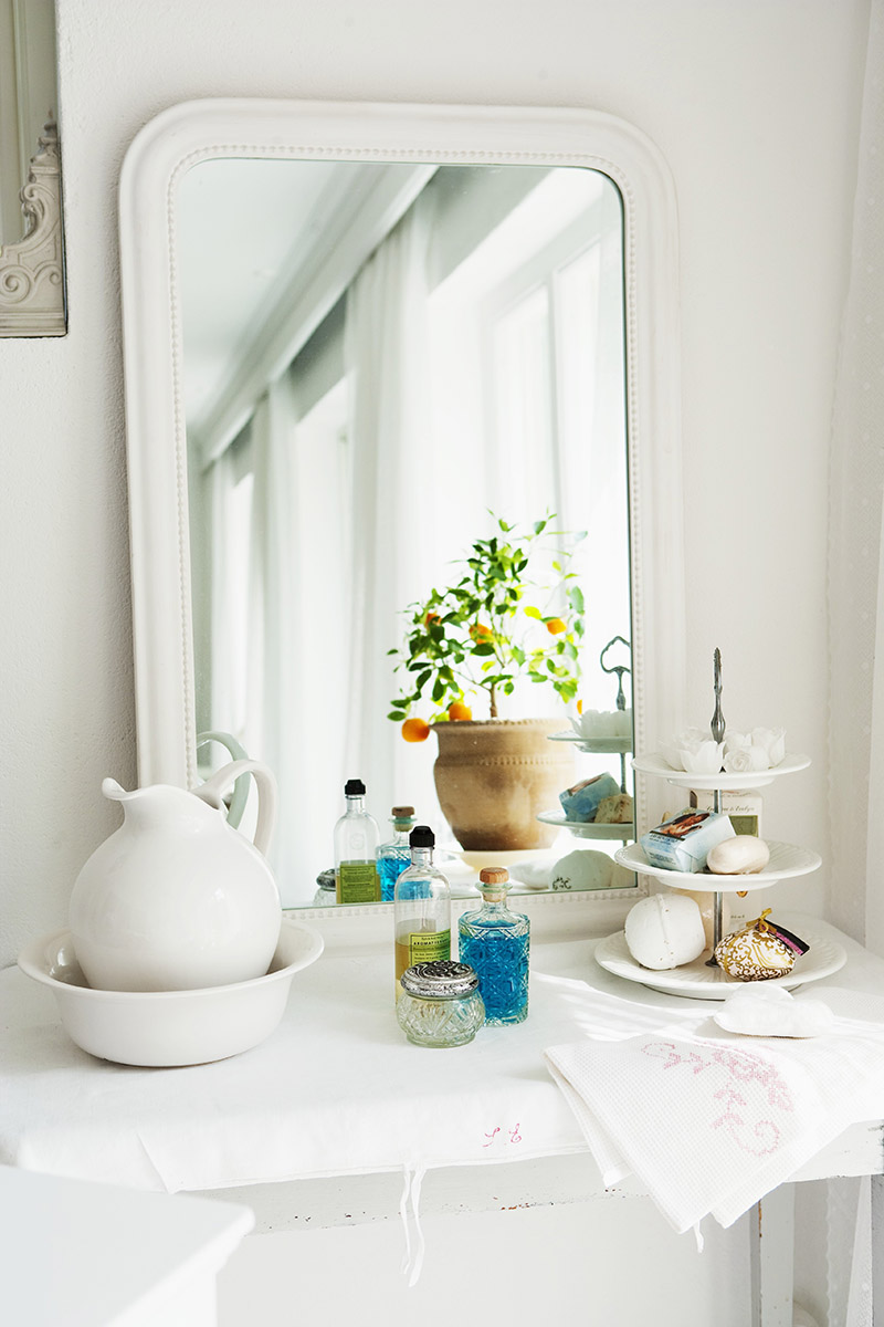 Mirror, washbasin and jug and soaps on cake stand in bathroom