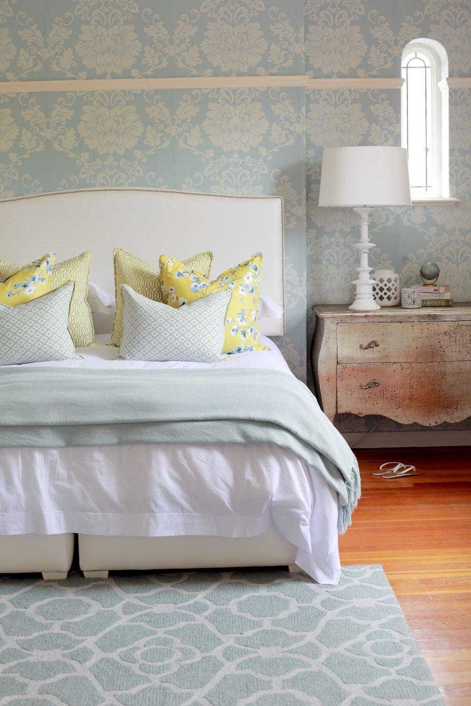 Tapete und Teppich in floralem Pastellblau, kombiniert mit dem zeitlosen Mustermix der Kissen auf einem Bett