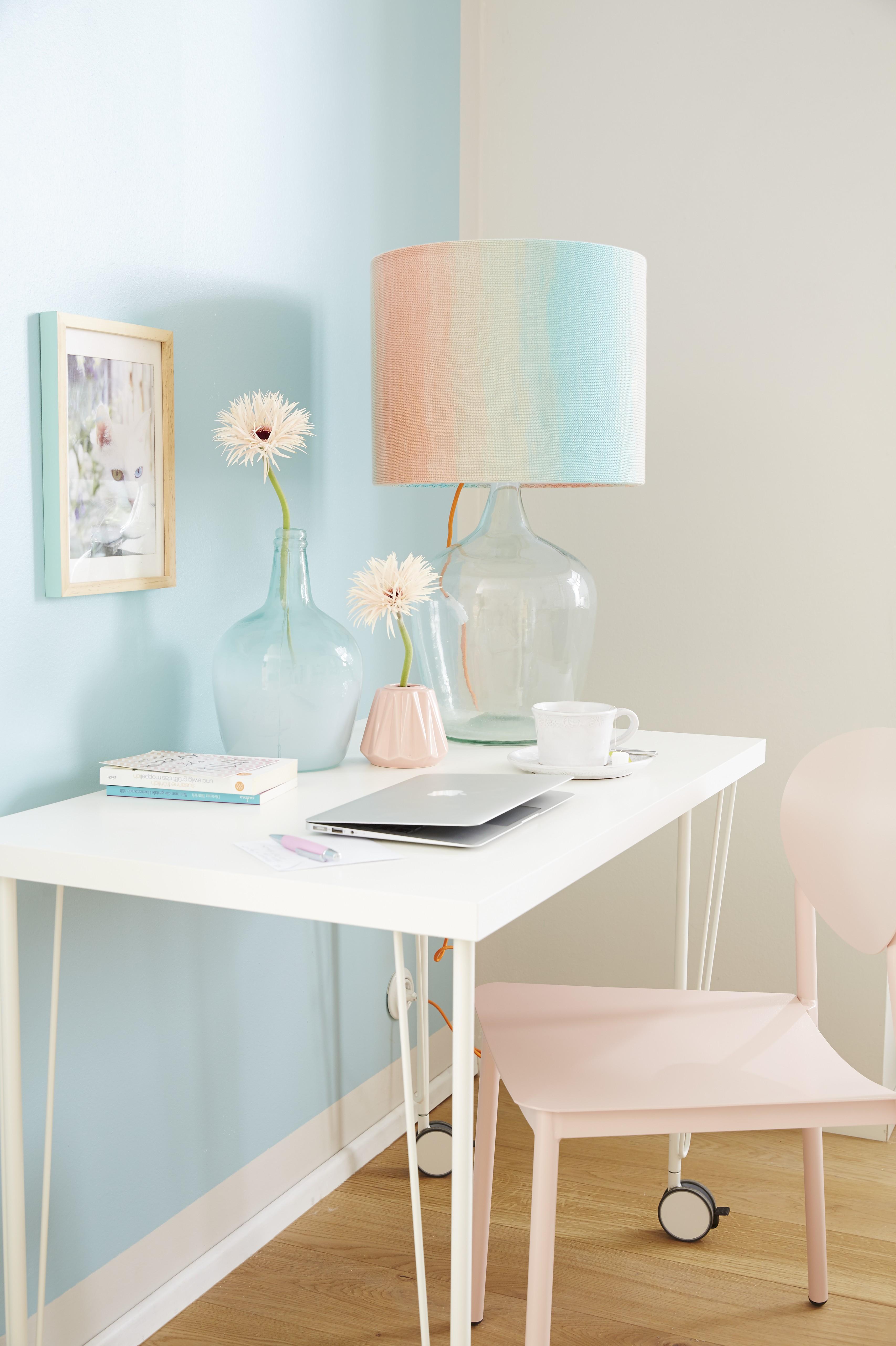 Schirm einer Tischlampe aus Strickgarn mit Farbverlauf, auf weissem Wandtisch